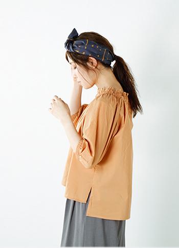 ギャザーをあしらい、絞ったネックラインが印象的。ややくすみのあるオレンジベージュがエスニックな気分を盛り上げてくれます。個性的な柄のヘッドアクセもポイントとなり、センス良くまとまっていますね。