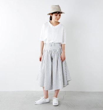 ストライプ柄のリネンパンツと白トップスを合わせた爽やかスタイル。パンツがボリューミーなときは、トップスをINすると野暮ったくならず、軽やかに着こなせます。