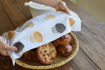 マフィンの手ぬぐいでパンをカバー。ユニークな図柄はアケモドロのラインナップから。ミョウガやコーヒー豆、パンなど、身近な図柄の一つ一つが美しい染めとシンプルな造形で表現されていて、贈り物にしたくなる手ぬぐいです。