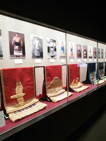 「相撲博物館」は、両国国技館1階にあり、入場無料です。 国技としての相撲資料を収集・保存する施設として昭和29(1954)年に開館、昭和60(1985)年両国国技館の開館と同時に移転。年6回の展示替があり様々な資料を見られます。こちらは歴代の横綱や力士のまわしの展示。 併設の売店では、相撲グッズなどがあり、面白いようですよ。 場所中は相撲の入場チケットが無いと、相撲博物館・売店とも入場できないので、ご注意下さい。