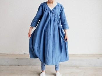 藍染めの色の良さが感じられるカシュクールドレス。ゆったりめに作られているので重ね着も◎ 胸元にあるギャザーがほどよいアクセントになり、あえてアクセサリーをつけないシンプルさがお洒落な着こなしを楽しめそうです。
