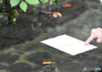 すぐ近くにある「水占斎庭(みずうらゆにわ)」の御神水に紙を浮かべると……。