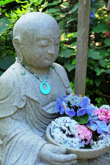 明月院の開山堂前に置かれた「花想い地蔵」。いつも季節の花を抱えていて、訪れる人の心をなごませてくれます。