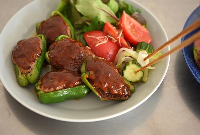 盛り付けはピーマンの肉詰めと副菜をワンプレートに。グリーンをベースに、トマトのアカがアクセントになって彩りもきれい。