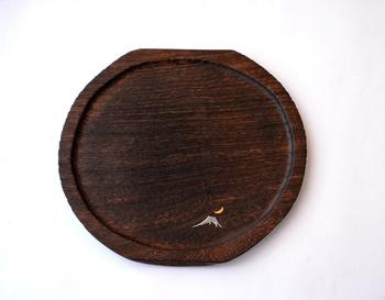 金沢の伝統工芸で作られた、桐の干菓子盆。表面を焼き上げた後で、煤を落として磨き上げるという、手間のかかった逸品です。