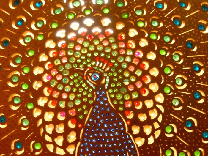少し絵柄に寄ってみましょう。  こちたは孔雀の柄のランプ。穴の大きさやカラーも様々で、とても繊細な手仕事です。