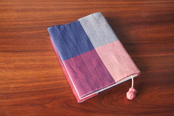 薄くてかさばらず本にフィットしてずれないブックカバーのレシピです。ボンボンつきで扱いやすいしおりの付け方も紹介されていますよ。
