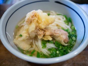 温かいうどんは「かけうどん」をベースに、トッピングによって、きつねうどん、天ぷらうどん、肉うどんなど。奇をてらったものではなく、ベーシックに美味しい物を提供しています。テーブルにある揚げ玉・しょうが・七味をお好みでかけて頂きます。 こちらは「とり天うどん」。鶏の天ぷらが3このってますが油のしつこさはなく、うどんのつゆにも合います。うどんはモチモチとした食感。美味しいお出汁も飲み干してしまう方も多いです。