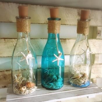 ボトルを並べて貝殻を飾るだけで、雰囲気のあるインテリアに。こちらはランプにもなっています。