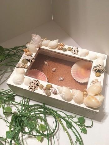 砂の上に、貝殻を閉じ込めたウッドボックス。2つある大きな貝殻に指輪を乗せて、リングピローとしても使えるアイデアグッズです。