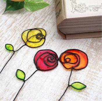 """ワイヤーと樹脂を使った""""ディップアート""""という手法で作られたバラのしおり。閉じた本の隙間から、キラキラ光るお花が顔を覗かせ、読書の時間にきらめきを与えてくれそう!"""
