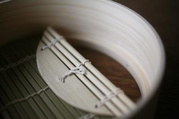 綺麗な檜でつくられていて、底は蒸気が通るように竹でできた簀の子(すのこ)になっています。この上に焼売や肉まん、冷ごはんなどを乗せて蒸します。 この蒸篭、なんと電子レンジでも使用することができるんですよ◎