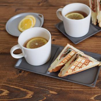 おかずを挟んだ食パンをカリカリに焼いて、ホットサンドに。2つに分かれたトレイにカップも一緒にのせれば、カフェのモーニングの用な雰囲気に♪一緒に添えるドリンクやスープにも、ひと工夫してみて。