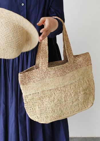 草木染綿糸編み込みで作られたさらりとしたラフィア素材のバッグ。 A4もすっぽり収まるサイズで、飲み物・日傘などつい荷物が増えがちな夏にぴったり。  飽きのこないシンプルなルックスも素敵。