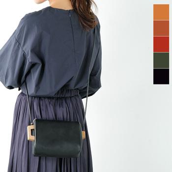 ふんわり丸みを帯びた形と両サイドのウッドパーツが個性的な小ぶりサイズのバッグです。ショルダーは細めのレザー紐で、やわらかいイメージのコーディネイトを邪魔しません。