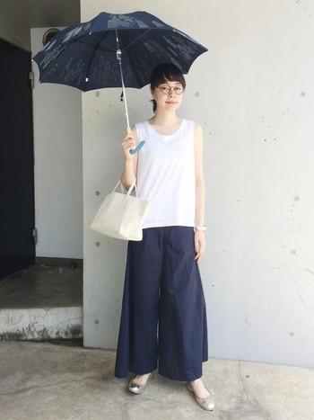 白いタンクトップにネイビーのワイドガウチョのシンプルなコーデ。ゴールドのフラットシューズと、キュートな刺繍の日傘で自分らしさをアピール。