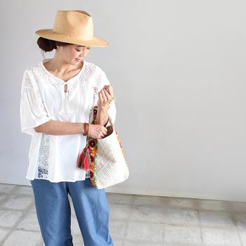 ゆるやかなシルエットのデニムに、レースブラウスが可愛らしい。バッグのカラフルな持ち手がキュートなアクセントになっています。