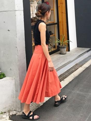 ビビッドカラーのスカートも、夏だからこそチャレンジしたいもの。大人っぽくまとめたいときは、写真のように黒やカーキなどのダークカラーで合わせると◎です。