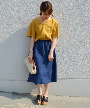 夏に履きたいリネンのフレアスカート。今年はデニムのような深い色合いのブルーをセレクトして。  トップスにはマスタードイエローのブラウスを。小物もクラッチバッグと甲を包むカバーサンダルを合わせれば、夏の旬コーデの完成です。