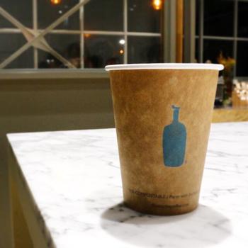 コーヒー界のサードウェーブと言われ、2015年に日本に上陸して話題になった『ブルーボトルコーヒー』。テイクアウト用カップは、ナチュラルなベージュのカップにちょこんと描かれたブルーのボトルが目を引くデザインです。