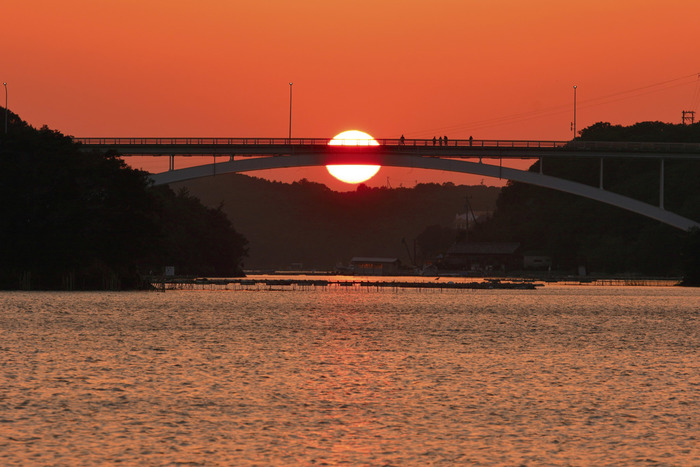 「賢島」は次期サミットが開催されることで注目を浴びている、観光地として開発された島です。賢島大橋は、志摩半島と賢島を結ぶ橋のことで、橋の上から見られる英虞湾に浮かぶたくさんの真珠のいかだは趣きがあります。  賢島大橋の上から望む英虞湾の夕景は、日本の夕陽100選にも選ばれています。