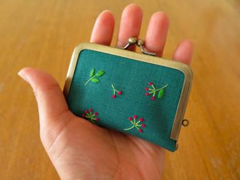 オリジナル刺繍を施した作品。ベリーのような実と葉っぱの手刺繍が可愛らしいですね。一見ミニサイズのがま口ポーチに見えますが…