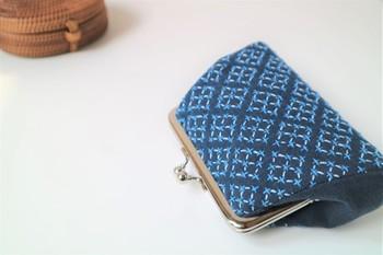 ひと針ひと針、伝統模様の「米刺し」を施したがま口のポーチ。紺地に2色のブルーの糸が爽やかな印象ですね。