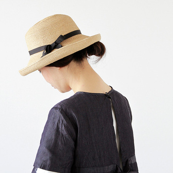 丸みのあるクラウンと、くるんとカールしたツバにセーラー帽のニュアンスを感じる麦わら帽子。ブラックの細いリボンが上品な可愛らしさを演出。大人っぽいコーデとも相性が良さそう。