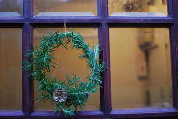 """ローズマリーのリースに松ぼっくりをあしらったシンプルなリースを玄関に飾って。丸い形のリースは「永遠」という意味をもつとか。ヨーロッパでは古くから、玄関にリースを飾るのは""""家族全員が無事に帰ってきますように""""というおまじないの意味があったそうですよ。"""