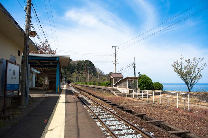 山陰本線沿線の鎧駅は、1912年に開業された日本海に面する無人駅です。日本昔話の挿絵のような景色にぽつんと佇む小さな無人駅は、哀愁が漂っており、その景観美からポスターやドラマの撮影舞台ともなっています。