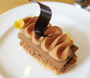 ■スペシャリテ(看板料理)の「ムッシュアルノー 」 ザクザクっとした食感が印象的なケーキ。チョコレートのプレートやナッツの生地、なめらかなチョコレートクリームに、オレンジの風味がアクセントになっています。