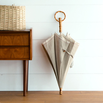 リネン無地のシンプルな日傘は、どんなコーディネートにも自然になじみます。輪っかになった竹の持ち手もポイント。腕に引っ掛ければ、両手が使えるという機能性もあります。