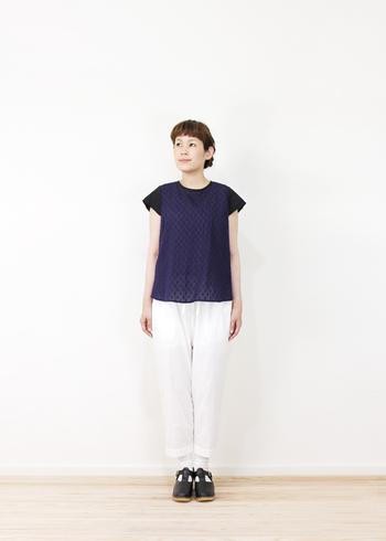 繊細なデザインの紺のブラウスは、袖と身頃が切り替えになっています。ディテールに凝ったブラウスは白パンツによく似合いますね。