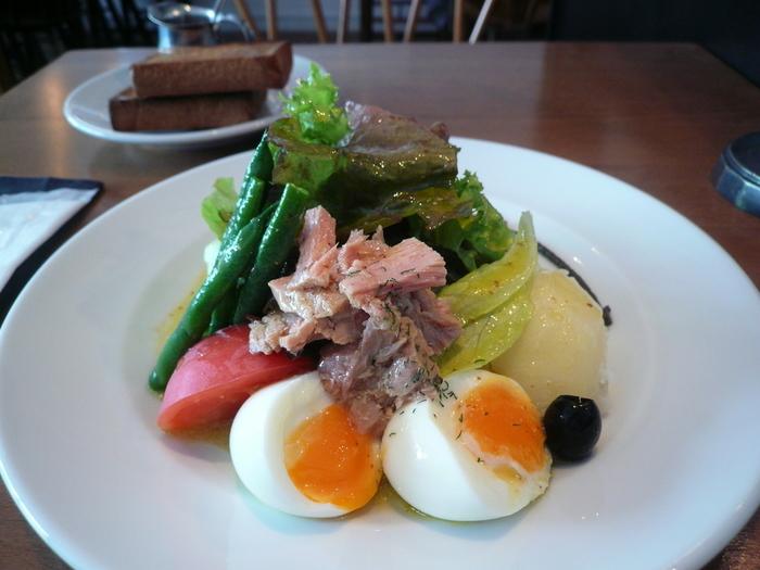 お店自慢のニース風サラダを目当てに訪れるひとも。具沢山の野菜に、半熟卵がそえられてボリュームたっぷりです。