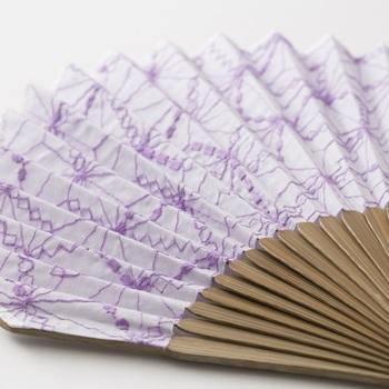 先染めのリネン生地に「遊 中川」の小紋柄、麻の葉をステッチで表現した扇子。やや縦長のホタテ形で、とても上品な印象。携帯に便利な共布の袋付きで、プレゼントにもおすすめです。