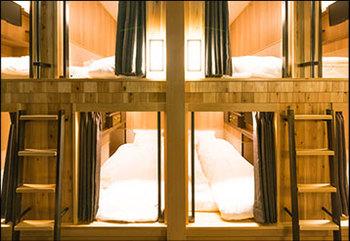 繭(POD)に包まれたような、一人でゆっくり快適にくつろげる宿泊スペースは3タイプあります。こちらは、スタンダードな縦型POD。温もりのある木にかこまれ、居心地の良い空間です。  館内は自分の利用フロア以外は立ち入りできないシステム。女性専用フロアもあり一人旅でも安心のセキュリティーです。
