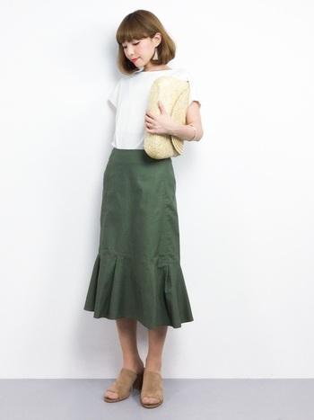 ヒップまわりはタイトに、膝下から大胆に広がるデザインのラッフルスカート。涼しげなサテン素材のホワイトシャツと合わせて上品な着こなしに。