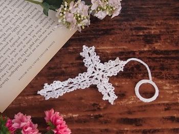 真っ白なレースで編んだ十字架のしおりには、丸いニットリングを編みくるんだものを付けて。本から垂れ下がる様子が可愛いらしく、指を引っ掛けて読書中の紛失防止にも役立ちます。糊付けなしの柔らかいコットン100%だから本にも手にも優しく馴染みます。