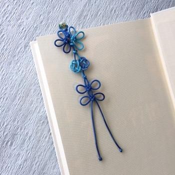"""グラデーションが美しい結び飾りのしおりは、""""つゆ結び""""でガラス玉を固定したあと""""几帳結び""""と""""あわじ結び""""を組み合わせ編んでいいるそう。しっかり結ばれた縁起のよい一品です。"""