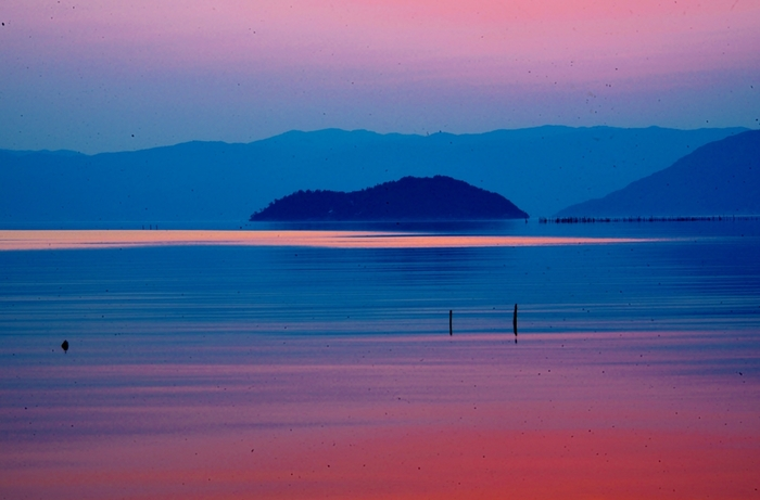 ピンク色の空と水色に浮かび上がる山々。優しく柔らかいものに包まれているような、穏やかな気持ちにさせてくれます。