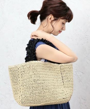ペーパー素材のカゴバッグは、軽くて持ち運びも楽ちん。取っ手のラッフルフリルがフェミニンな印象を与えてくれます。