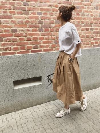 ベージュのコットンフレアースカートが印象的なワントーンコーデです。スニーカーとシャツのトーンを合わせて統一感を出して。