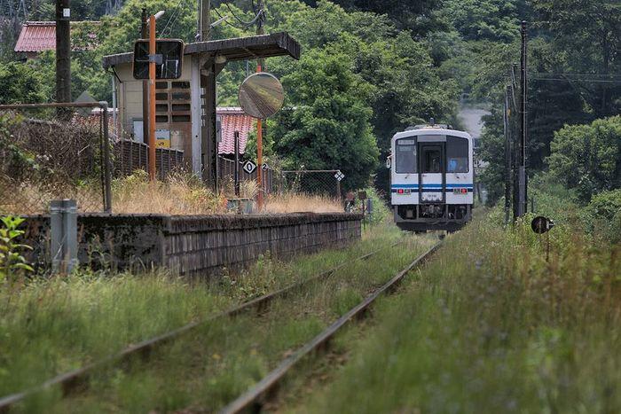 江の川畔を走る三江沿線の明塚駅は、1967年に開業された無人駅です。農地と森に囲まれた小さな古びた駅構内には、駅舎も待合室も無く、小さな屋根付きのベンチがあるのみです。草に覆われた線路、駅へ乗り入れる列車、古びたホームが融和した景色は、訪れる人を魅了してやみません。