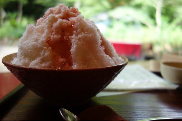 「氷室の氷・いちごみるく味」は、練乳のかかったふわふわの氷に、しっかりと苺の味のするシロップをかけていただきます。 氷は雪のようにきめがこまかく、口の中ではかなく溶けます。  緑陰を眺めながらいただく甘いものが、歩き疲れた体に染み渡ります。「抹茶小豆味」もありますよ。