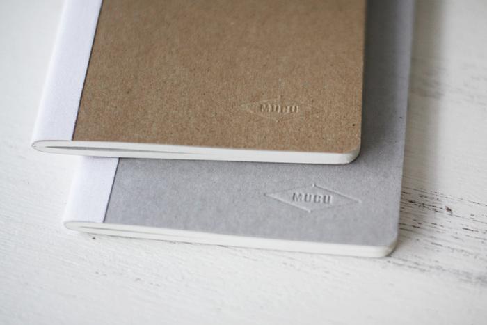 「無垢」からくる名前のとおり、デザインも機能も限りなくシンプルなノート。表紙には、表紙装丁の芯地に使われる「チップボール」を使用。背表紙のキャンバス地部分は職人が1枚1枚裁断・手張りを行っています。