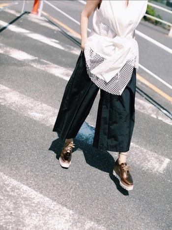 デザイン性の高い白シャツは、シンプルに黒のコットンパンツと合わせて。さらに、ブロンズカラーの靴でモードっぽく大人の味付けを。