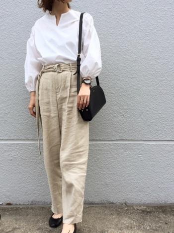 バルーン袖の白シャツは、ベルト付きのパンツにイン。黒のバッグと靴で程よく引き締めた大人の甘辛コーディネートです。