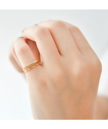 華奢なデザインの指輪を2つ組み合わせて。細めのものの重ねづけは、手元を女性らしく見せてくれます。