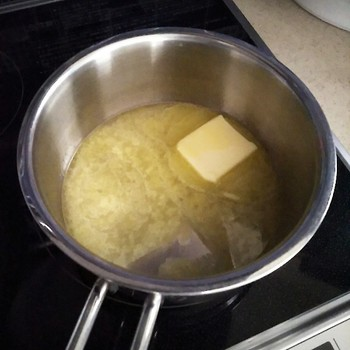 ここからは手早く作業を。バターと水と塩を鍋に入れて、溶けたら強火で一気に沸騰させます。完全に溶けて細かい白い泡がたってきたら火をとめ、ふるった薄力粉を一気に加えます。  まとまるまで一気にヘラで混ぜ、中火で30秒ほど練ります。 艶が出たら火からおろし、溶き卵を半量加えて手早く混ぜます。
