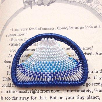 半月形のリングを使って作られているブローチです。色がグラデーションになった富士山の繊細な刺繍は見惚れてしまいます。